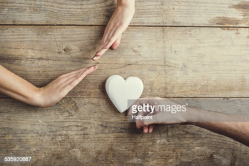 Man offering a heart to a woman. : Stock Photo