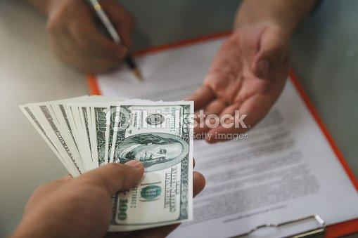 Homme offrant lot de cent billets d'un dollar. Gros homme d'affaires signature contrat fait un Pacte, Détails du contrat entreprise. : Photo