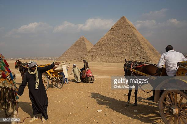 A man offering camel rides talks with tourists in front of Egypt's famous Giza Pyramids on December 18 2016 in Cairo Egypt Since the 2011 Arab Spring...