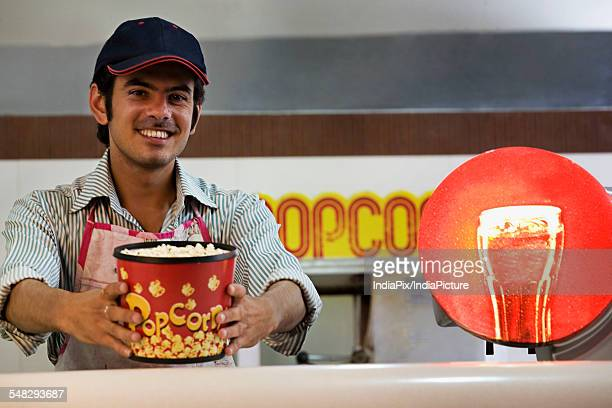Man offering popcorn at a counter