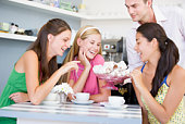 Man offering sweet treats to three young women