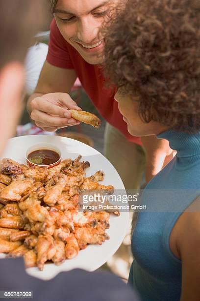 Man offering woman a taste of chicken wing