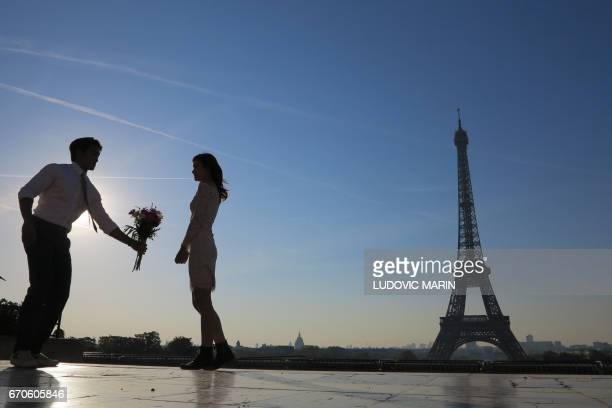 A man offers a bouquet of flowers to his fiancee at sunrise on the Human Rights plaza facing the Eiffel Tower at the Trocadero on April 20 2017 in...
