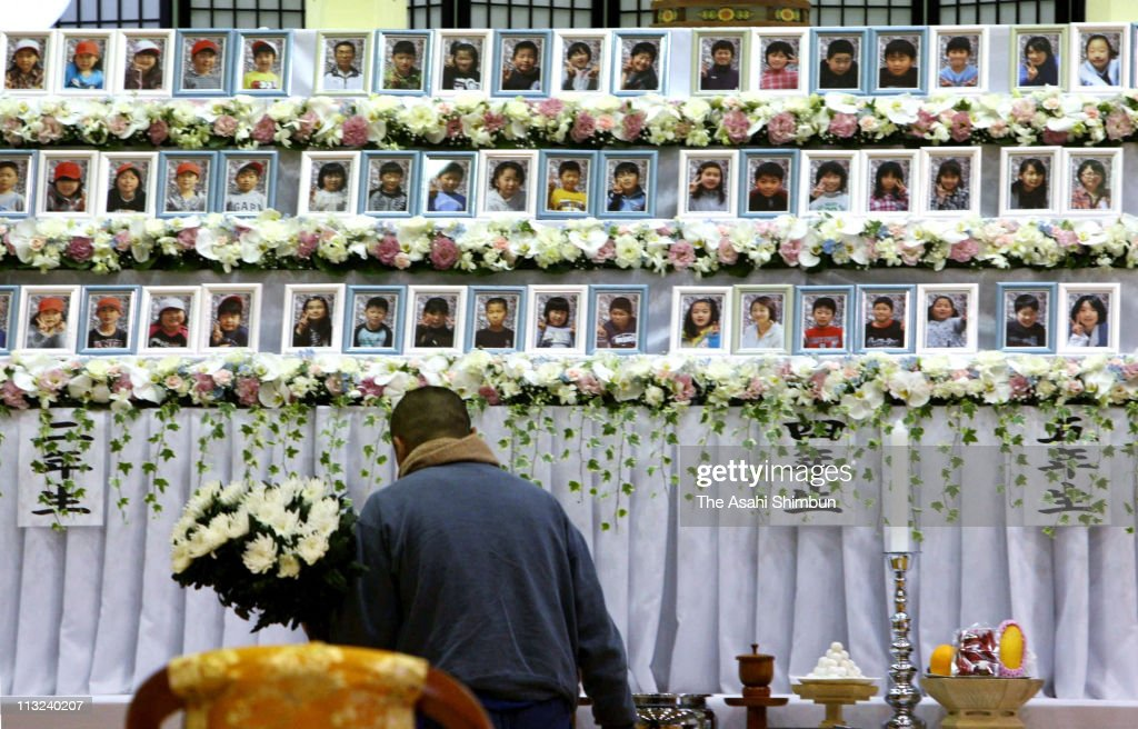 A man offers a flowers at a stand which displays portraits of Okawa Elementary School pupils during the joint memorial service at Iinokawa Daini Elementary School on April 28, 2011 in Ishinomaki, Miyagi, Japan. 74 out of 108 pupils of the school were killed by the tsunami. The government's construction of temporary housing in areas devastated by the March 11 magnitude 9.0 earthquake and tsunami continues as many residents remain in temporary evacuation shelters.