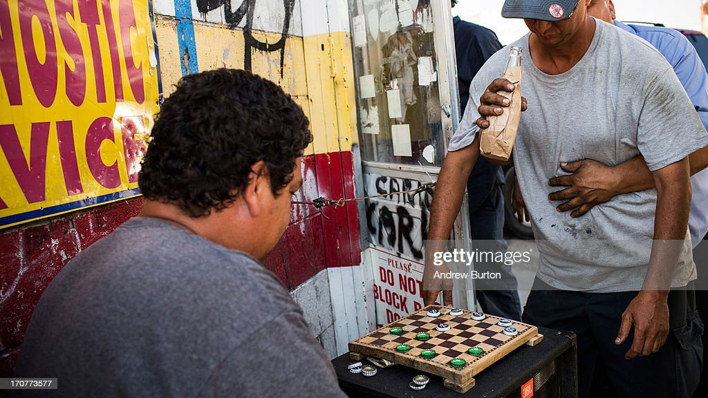 A man offers another man a drink of beer while he plays checkers after a day of work on June 17, 2013 in the Willet's Point neighborhood of the Queens borough of New York City. The Willet's Point Neighborhood, also known as the Iron Triangle, is situated directly next to Citi Field, where the Met's play baseball, and is known for both its car repair shops and lack of paved roads. The future of the neighborhood has been a contentious issue between residents and the city, as the city hopes to further develop the land despite protests from its residents.