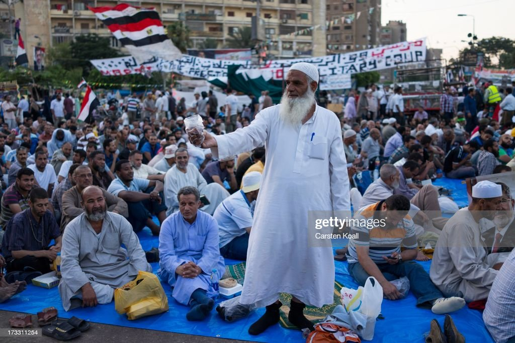 A man offers dates as supporters of ousted president Mohamed Morsi pray before breaking the daily Ramadan fast on the second day of Ramadan, the sacred holy month for Muslims where many will fast from sun-up to sun-down on July 11, 2013 in Cairo, Egypt. Egypt continues to be in a state of political paralysis following the ousting of former President and Muslim Brotherhood leader Mohamed Morsi by the military. Adly Mansour, chief justice of the Supreme Constitutional Court, was sworn in as the interim head of state in a ceremony in Cairo on the morning of July 4.