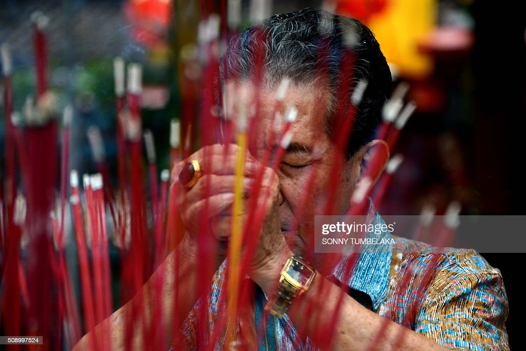 A man offers prayers on the first day of the Lunar New Year of the Monkey at the Dharmayana temple in Kuta, near Denpasar on Indonesia's Bali island on February 8, 2016. The Lunar New Year is celebrated in many parts of the predominantly Muslim country of 250 million people where Chinese heritage took roots through ancient transmigration. AFP PHOTO/SONNY TUMBELAKA / AFP / SONNY TUMBELAKA