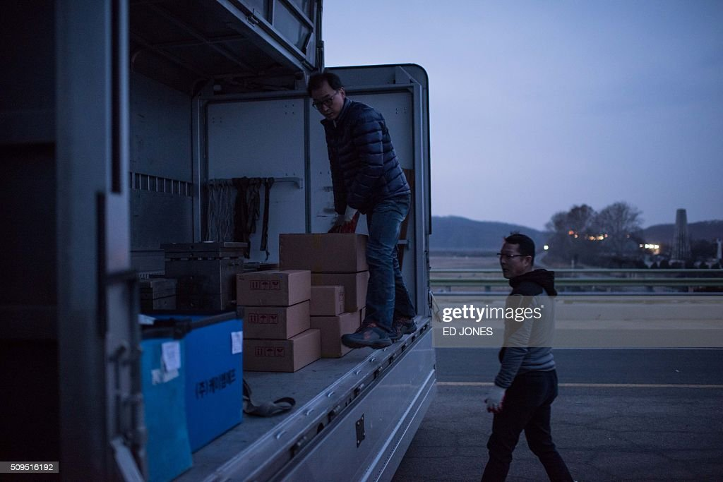 A man offloads boxes from a vehicle which arrived from the Kaesong joint industrial on a roadside after a checkpoint near the Demilitarized Zone (DMZ) separating the two Koreas in Paju on February 11, 2016. North Korea on February 11 expelled all South Koreans from the jointly-run Kaesong industrial zone and seized their factory assets, saying Seoul's earlier decision to shutter the complex had amounted to a 'declaration of war'. AFP PHOTO / Ed Jones / AFP / ED JONES