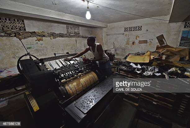 A man oils parts of an old original Heidelberg printing press at the Daha printing press in Mogadishu on March 26 2015 The vintage Germanbuilt...