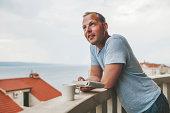 Man on a balcony at hotel in Croatia