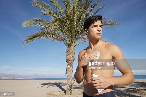Man on a beach applying sun block lotion to himself