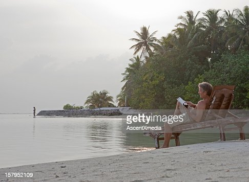 A man on a beach chair using a digital tablet : Stock Photo