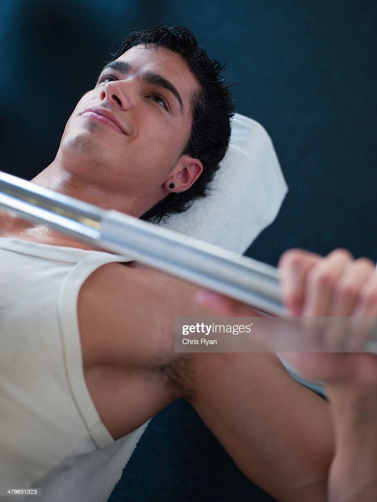 Man on a bench getting ready to lift free weights : Stock Photo