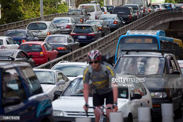 Man on a bicycle in the rush hour with much traffic on November 25 2010 in Auckland New Zealand North Island