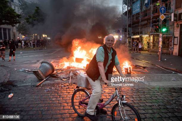 A man on a bicycle looks to the street with fires burning behind him during a demonstration against the G20 Summit on July 7 2017 in Hamburg Germany...
