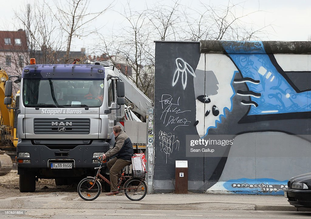 A man on a bicycle rides past as a truck maneuvers on a construction site next to the East Side Gallery, which is the longest still-standing portion of the former Berlin Wall, where a new hotel is scheduled to be built on February 28, 2013 in Berlin, Germany. According to media reports the developer in charge of the project plans to remove an approximately 25-meter long piece of the Wall and transfer it elsewhere in order to allow access to the construction site. Critics, including East Side Gallery mural artists and Spree River embankment development opponents, decry the move, citing the East Side Gallery's status as a protected landmark and a majortourist attraction.