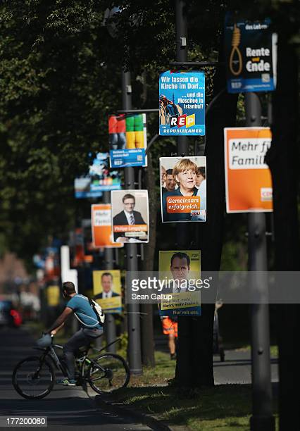 A man on a bicycle rides past election campaign posters including one featuring German Chancellor and Christian democrat Angela Merkel hanging from...
