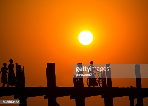 man on a bicycle stops on U Bein Bridge at sunset : Stock Photo