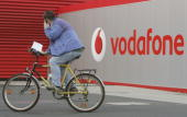 A man on a bicycle talking on a mobile phone drives past a sign announcing the Vodafone stand at the CeBIT technology fair March 15 2007 in Hanover...