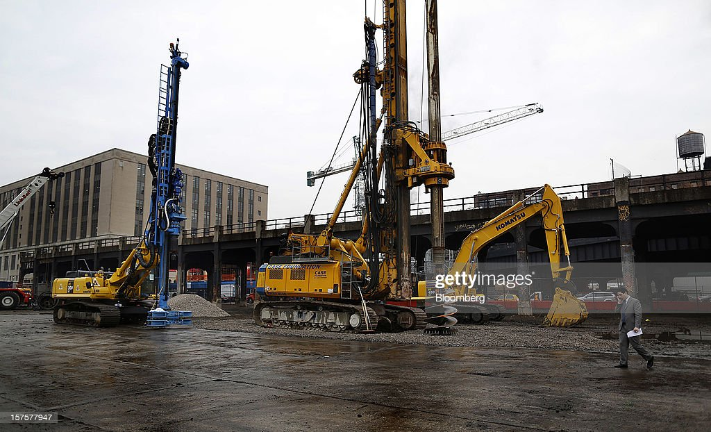 A man on a cell phone walks past a Komatsu Ltd. excavator before the start of the groundbreaking ceremony for the Hudson Yards development in New York, U.S., on Tuesday, Dec. 4, 2012. Related Cos. has tentative deals in place for two more tenants to occupy the first tower of its Hudson Yards development, Chairman Stephen Ross said today as construction began at the 26-acre site on Manhattan's west side. Photographer: Victor J. Blue/Bloomberg via Getty Images