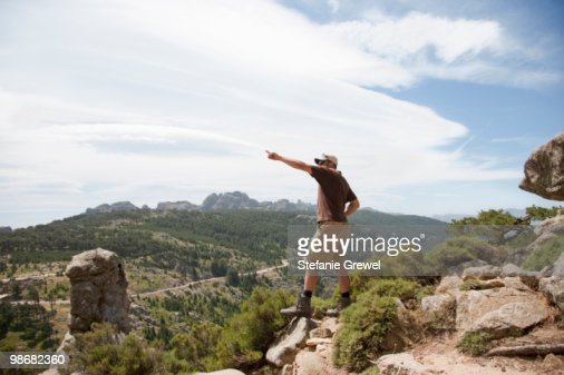 Man on a cliff pointing : Stock Photo