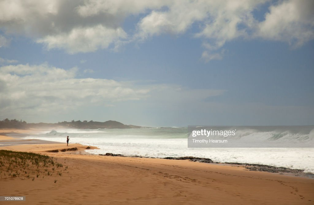 Man on a deserted sandy beach looking out to sea : Stock Photo