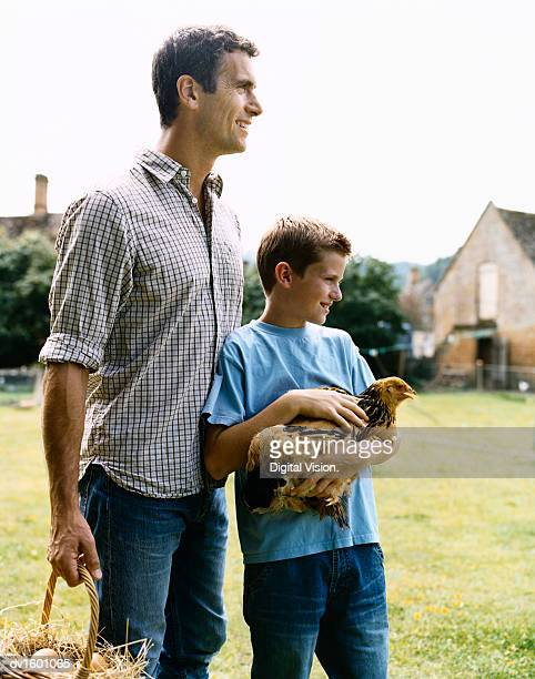 Man on a Farm Holding a Basket of Eggs and His Son Holding a Hen
