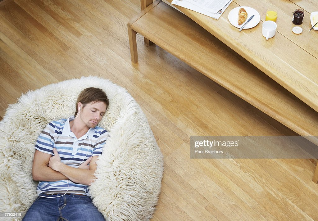 Man on a furry bean bag chair wearing earbuds : Stock Photo