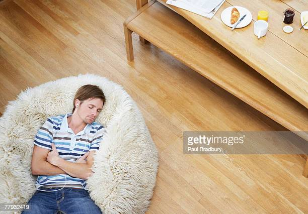 Man on a furry bean bag chair wearing earbuds