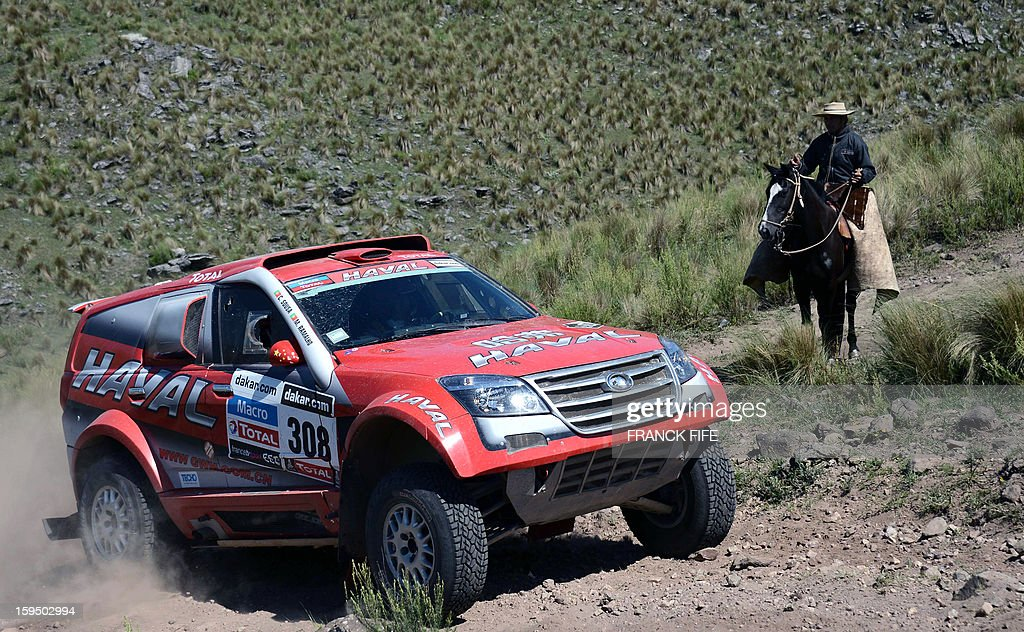 A man on a horse looks at Portuguese Great Wall driver Carlos Sousa during the Stage 9 of the Dakar 2013 between Tucuman and Cordoba, Argentina, on January 14, 2013. The rally takes place in Peru, Argentina and Chile between January 5 and 20. AFP PHOTO / FRANCK FIFE