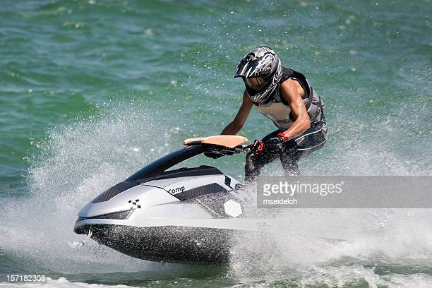 A man on a jet ski going through water with a helmet on