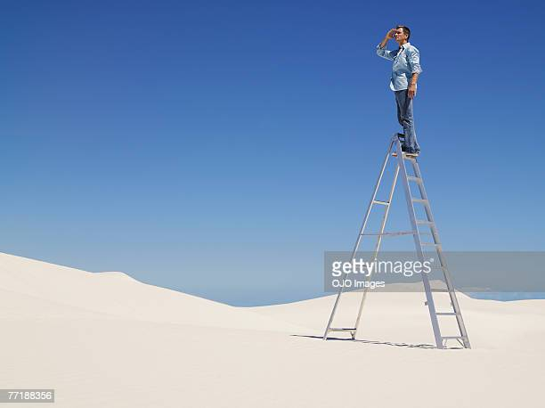 A man on a ladder in the desert