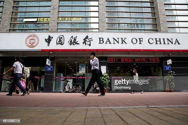 A man on a mobile phone walks past a Bank of China Ltd branch in Guangzhou Guangdong Province China on Thursday March 27 2014 Bank of China Ltd the...