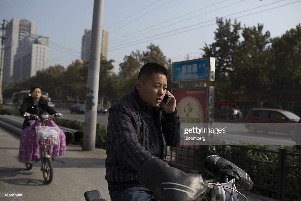 A man on a motorbike talks on a mobile phone in Jinan, China, on Wednesday, Nov. 6, 2013. The third plenary session of the 18th Communist Party of China Central Committee will be held from Nov. 9 to Nov. 12 in Beijing. Photographer: Brent Lewin/Bloomberg via Getty Images