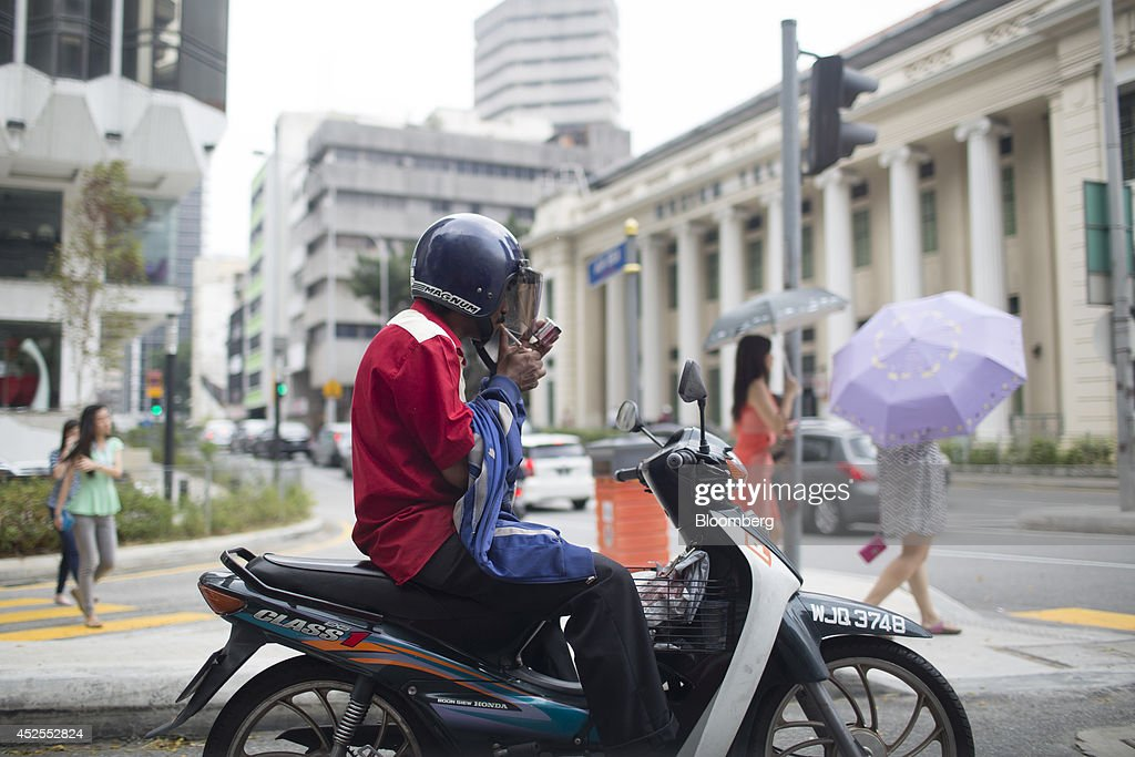 A man on a motorcycle lights a cigarette in Kuala Lumpur, Malaysia, on Tuesday, July 22, 2014. Malaysian Airline System Bhd. (MAS), reeling from its second disaster in four months, plans to present a revival plan to its state-run parent Khazanah Nasional Bhd. this week, people familiar with the matter said, amid reports the national carrier is likely near the end of its days as a publicly traded company. Photographer: Brent Lewin/Bloomberg via Getty Images