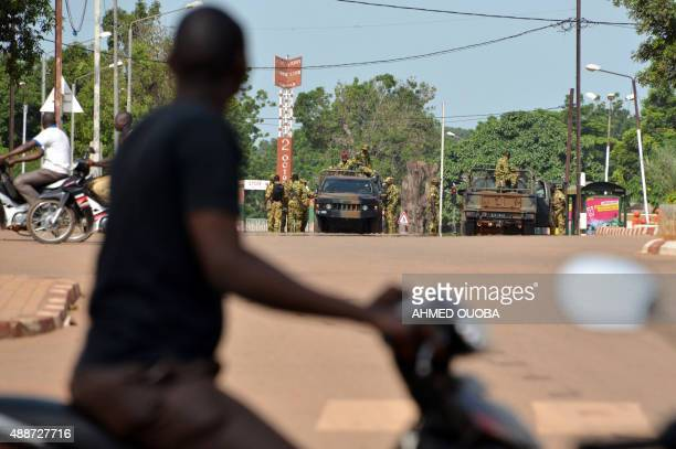 A man on a motorcycle looks at Burkina Faso's troops standing guard at near Nation Square in Ouagadougou on September 17 2015 Burkina Faso's...