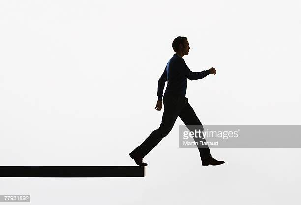 Man on a plank about to walk over ledge
