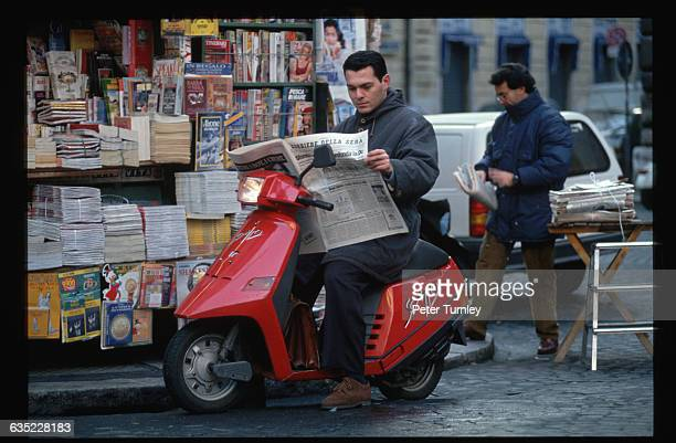 A man on a red scooter reads the newspaper at a stand in Piazza Navona