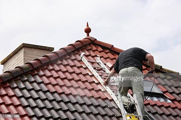 Mann auf dem Dach, die Reinigung mit dem Hochdruckreiniger Fliesen
