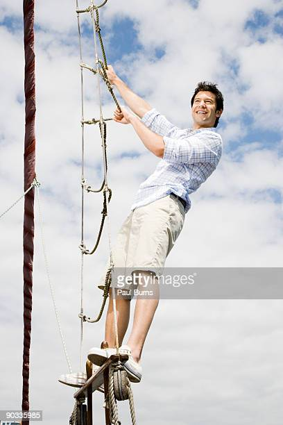Man on a Sailboat Climbing a Rope Ladder