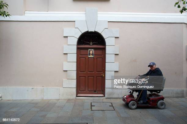 A man on a scooter passes by a door with a picture of Jesus Christ on it in the street on April 3 2017 in Gibraltar Tensions have risen over Brexit...