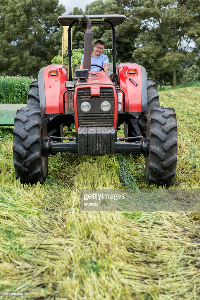 Guy On Tractor : Man on a tractor working at the farm stock photo getty