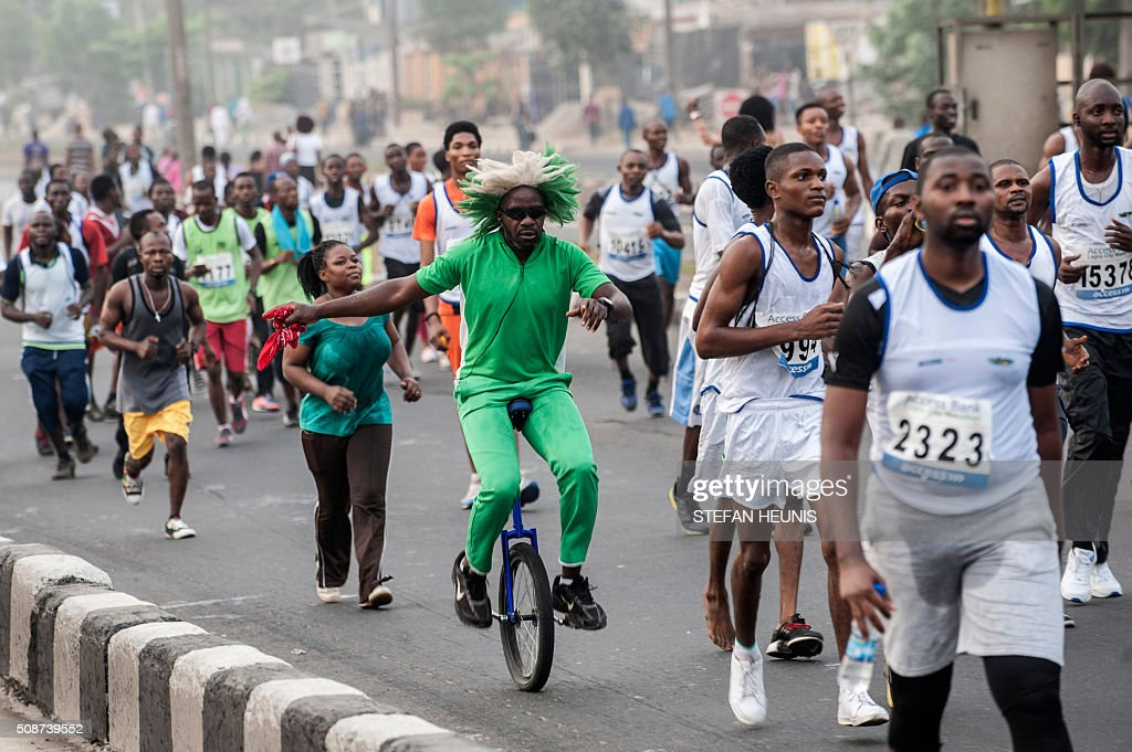 A man on a unicycle participates in the Access Bank Lagos City Marathon on February 6, 2016. The Lagos City Marathon is one of the biggest races in Nigeria in over 30 years and attracted elite African long distance athletes and over 20,000 participants. / AFP / STEFAN HEUNIS