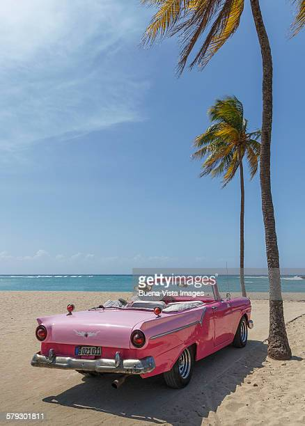 Man on a vintage car on the beach