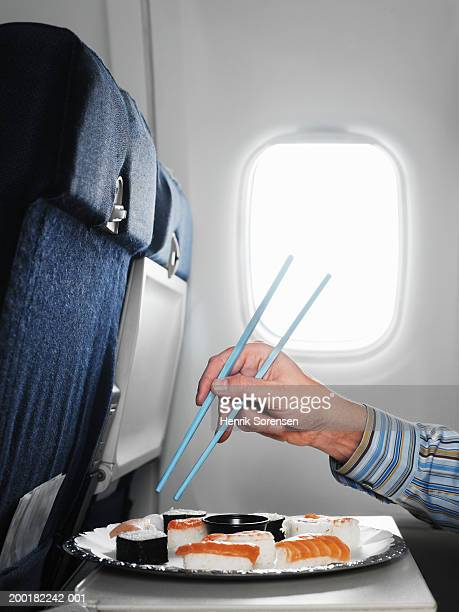 Man on aeroplane reaching for sushi with chopsticks, close-up