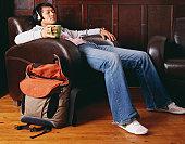 Man on armchair, holding mug, wearing headphones, eyes closed