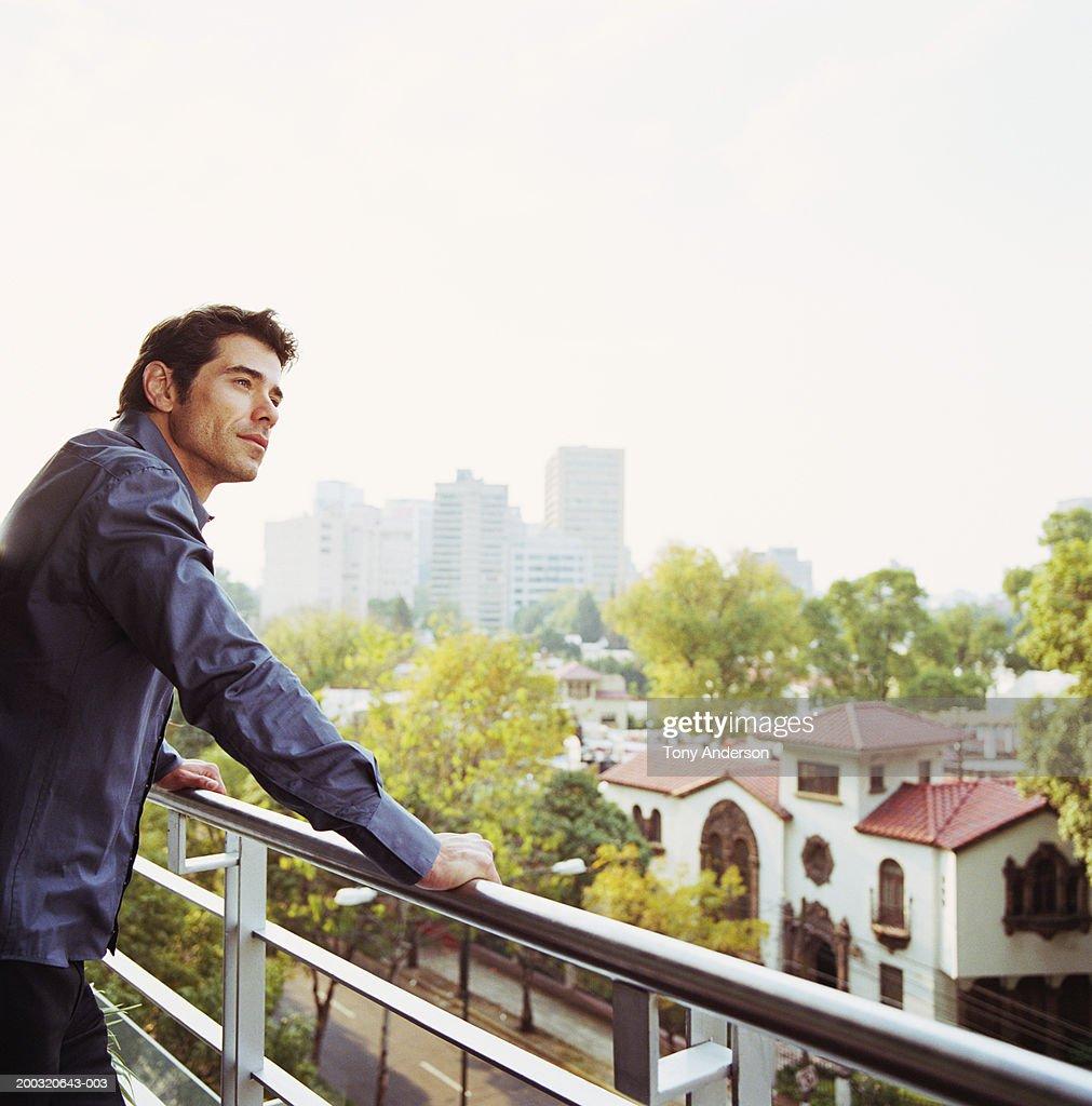 Man on balcony looking at scenery