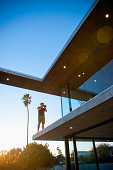 man on balcony photographing Modernist home