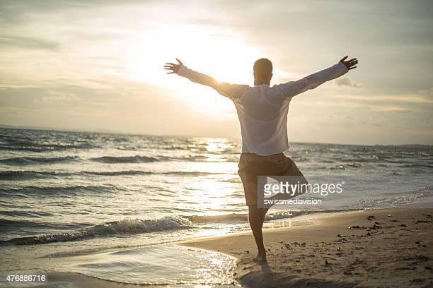 Homme sur la plage au coucher du soleil l'exercice de yoga et de méditation