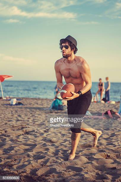 man on beach catching football